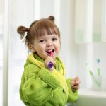 Smiling child kid little girl brushing teeth in bath